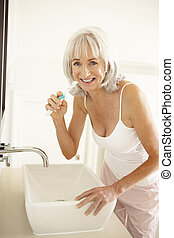 Senior Woman Brushing Teeth In Bathroom