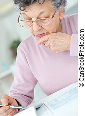 senior woman calculating taxes at home
