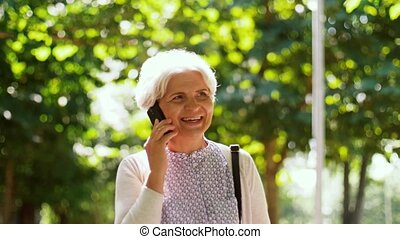 senior woman calling on smartphone in park - retirement,...