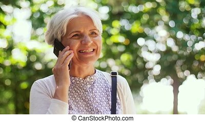 senior woman calling on smartphone in park - retirement,...