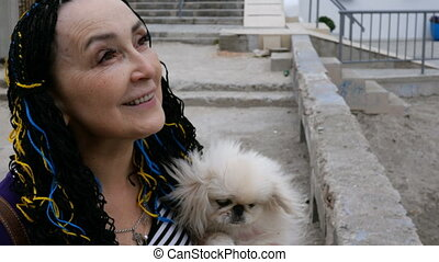 Senior woman Caucasian ethnicity holds her dog in her arms....