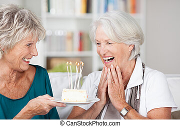 Senior woman celebrating her birthday being handed a cake with burning candles by her friend and clapping her hands in surprise and appreciation