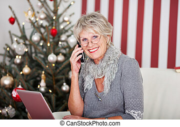 Senior woman chatting on the phone at Christmas - Senior ...
