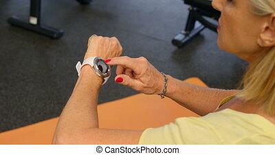 Senior woman checking her smartwatch in fitness studio 4k