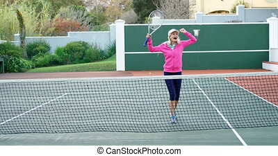 Senior woman cheering in tennis court 4k - Happy senior...