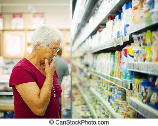 Senior woman choosing a dairy products at supermarket