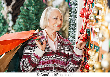 Senior Woman Choosing Christmas Ornaments