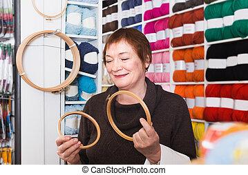 Senior woman choosing embroidery hoops for fancywork in needlework shop