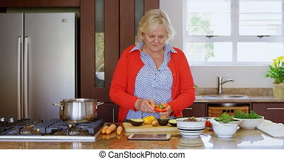 Senior woman chopping vegetable in kitchen 4k - Senior woman...