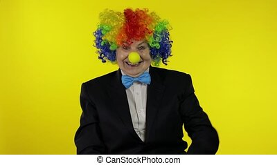 Senior woman clown in wig having fun, smiling, waves her hands, show thumb up