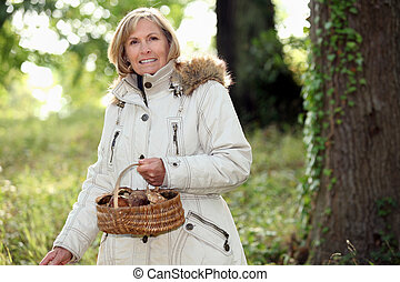 Senior woman collecting mushrooms in the woods