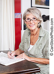 Attractive senior woman wearing glasses completing a crossword puzzle sitting at a small wooden table in her house