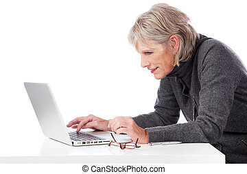 Senior woman concentrating when using her laptop