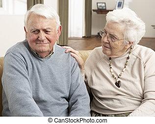 Senior Woman Consoling Husband At Home