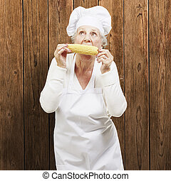 senior woman cook eating a corncob against a wooden ...