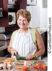senior woman cooking in kitchen - happy senior woman cooking...