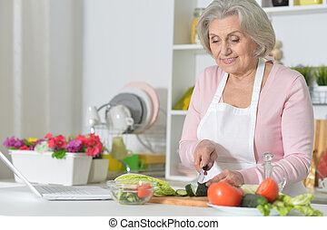 Senior woman cooking in kitchen - Senior woman with grey...