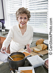 Senior woman cooking soup in kitchen