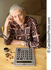 Senior woman counting coins - Senior woman counting money...