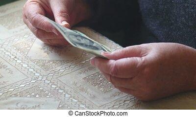 Senior woman counting dollar banknotes, closeup.