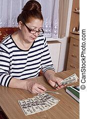 Senior woman counting savings money
