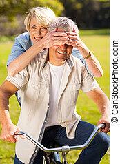 senior woman covering husband's eyes on bike