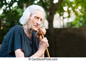 Senior woman crying with a walking cane