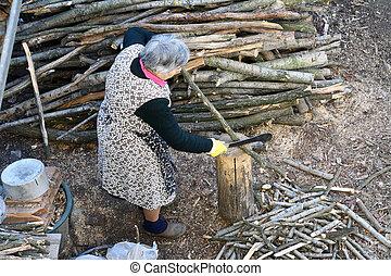 Senior woman cutting wood