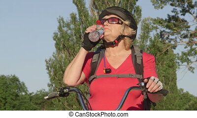 Senior woman cyclist on a bicycle drinking water from bottle