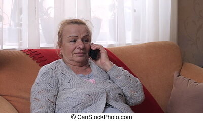 Senior woman dialing the number on phone and then talking