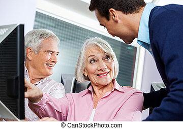Senior Woman Discussing Teacher In Computer Class