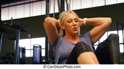 Senior woman doing abs workout in fitness studio 4k -...