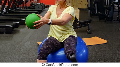 Senior woman doing abs workout with exercise ball 4k -...