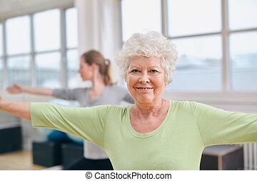 Senior woman doing aerobics exercise at gym