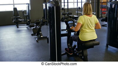 Senior woman doing back exercise on machine in fitness...
