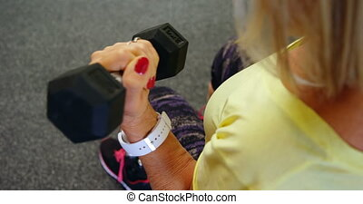 Senior woman doing biceps workout with dumbbell in fitness...