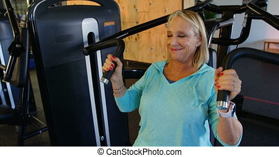 Senior woman doing exercise on chest press machine 4k -...