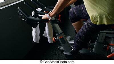 Senior woman doing exercise on exercise bike 4k