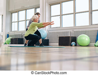 Senior woman doing exercise with her personal trainer at...