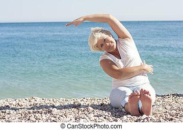 Senior woman doing gymnastics exercises on the beach