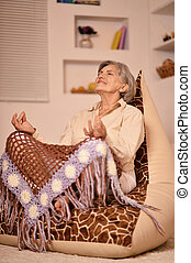 Senior woman doing meditation at home