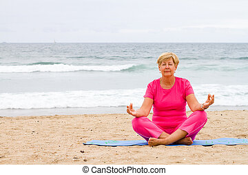 senior woman doing meditation on beach