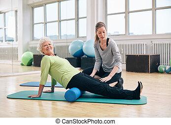 Senior woman doing pilates with foam roller