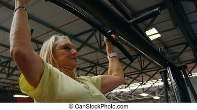 Senior woman doing pull-ups in fitness studio 4k -...