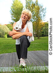 Senior woman doing sport with towel over neck