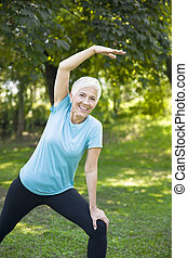 Senior woman doing streching exercise in the park