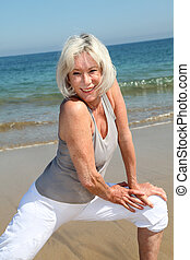 Senior woman doing stretching exercises on the beach