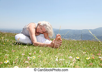Senior woman doing stretching exercises in countryside