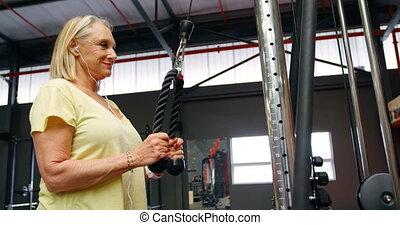 Senior woman doing triceps exercise in fitness studio 4k -...