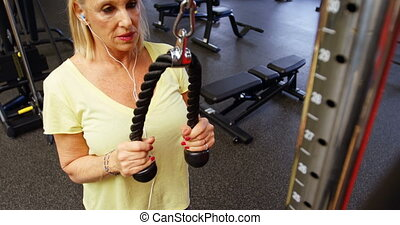 Senior woman doing triceps exercise in fitness studio 4k -...